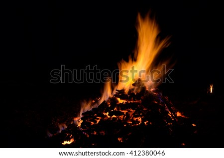 beautiful red hot glowing ember pile with colorful flames in winter night