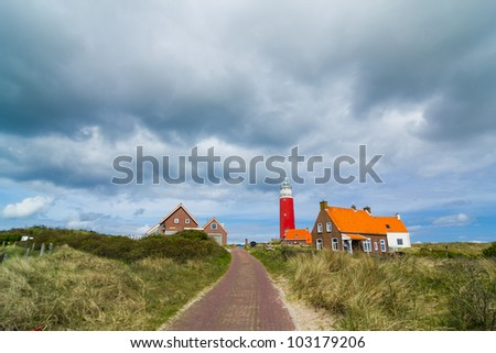 Beautiful red Lighthouse with road, island Texsel, Netherlands. Panorama - stock photo