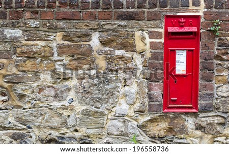 Beautiful red mailbox built into a stone wall, seen in Rye, Kent, UK. - stock photo