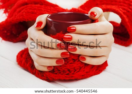 beautiful red manicure with a cup of tea on the white wooden table.