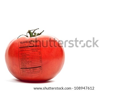 Beautiful red ripe tomato with a nutrition label ready to be eaten - stock photo