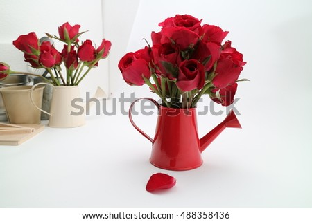beautiful red rose with in red watering can on white background