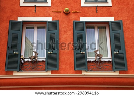 Beautiful red stucco house with old french green shutter windows, Monaco, Monte Carlo. - stock photo