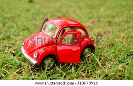 Beautiful red toy car park on grass field - stock photo