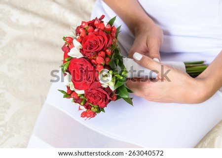 Beautiful red wedding bouquet of roses and freesia flowers in hands of the bride - stock photo
