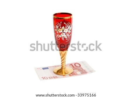 Beautiful red wine glass  with golden stem on ten euro bill isolated - stock photo