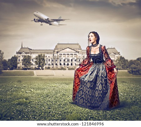 Beautiful red woman, on the lawn of a palace, with a historical dress while an airline is flying in the sky - stock photo