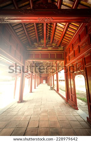 Beautiful red wooden hall with golden ornate details in Hue citadel, Vietnam, Asia. Vanishing roof and tiled floor. Sunlight through columns. Famous destination for tourists. UNESCO Heritage site. - stock photo