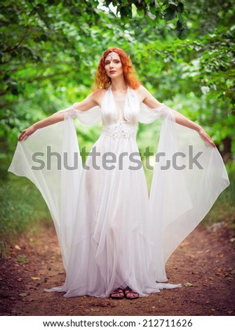 Beautiful redhead elf woman wearing white dress in the garden - stock photo