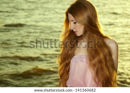 Beautiful redhead girl at pond. Beauty summertime - stock photo