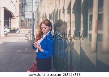 Beautiful redhead girl in blue jacket posing in an urban context