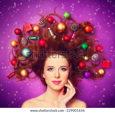 Beautiful redhead girl with christmas toys on violet background. - stock photo