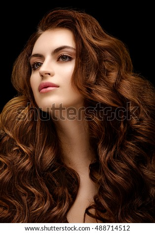 Beautiful redhead girl with evening make-up and long wavy shiny hair. Fashion photo. Beauty portrait. Headshot. Picture taken in the studio on a black background. Natural beauty.