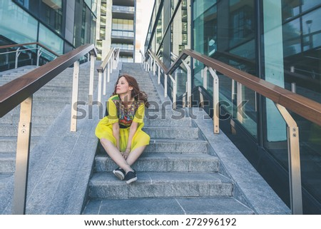Beautiful redhead girl with long hair and blue eyes posing in an urban context - stock photo