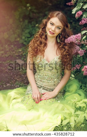 Beautiful redhead girl with long wavy curls in a beautiful green dress sitting in the park among the lilacs