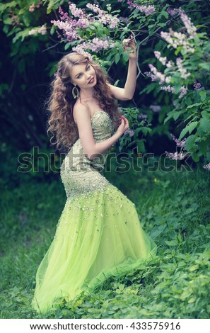 Beautiful redhead girl with long wavy curls in a beautiful green dress walk in the park among the lilacs - stock photo