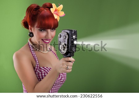 Beautiful redhead pin up girl with vintage camera - stock photo