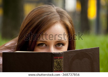 Beautiful redhead woman hiding behind the book in park