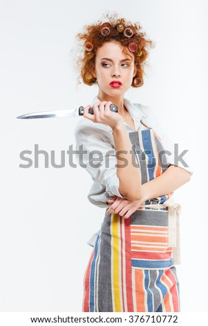 Beautiful redhead woman in apron holding knife isolated on a white background - stock photo