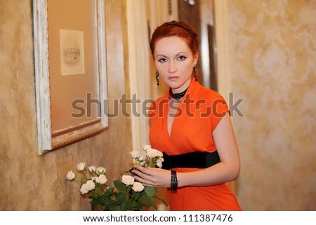 Beautiful redhead woman in classic luxury interior - stock photo