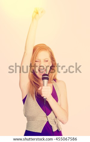 Beautiful redhead woman singing with microphone - stock photo