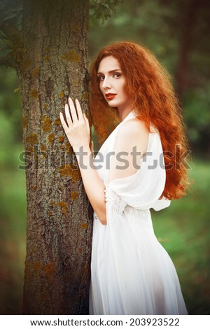 Beautiful redhead woman wearing white dress stands near the tree - stock photo