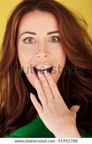 Beautiful redhead woman with her hand to her mouth and wide eyes in a shocked expression - stock photo