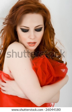 Beautiful redhead woman with red material - stock photo