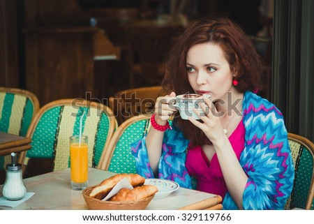 Beautiful redhead women sitting in cafe in Paris - stock photo