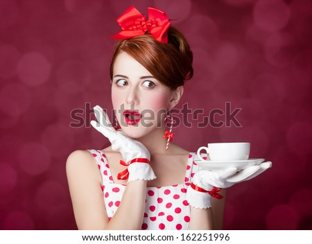Beautiful redhead women with cup of tea. Photo in retro style with bokeh at background. - stock photo