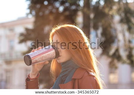 Beautiful redhead young lady with long hair in leather jacket and scarf drinking coffee from tumbler - stock photo