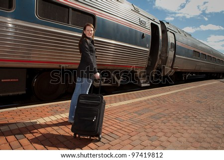 Beautiful redheaded traveler about to board a modern train