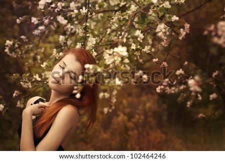 beautiful redheaded woman in a spring garden - stock photo