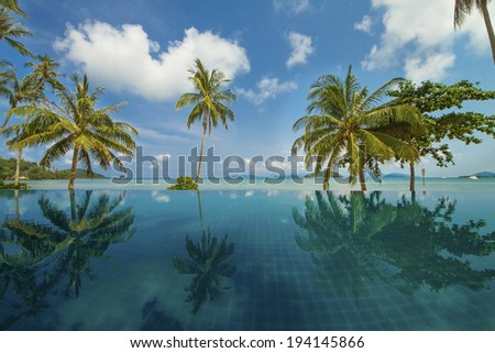 Beautiful reflection of coconut trees and blue sky on the swimming pool at the beach, Mak Island, Thailand  - stock photo