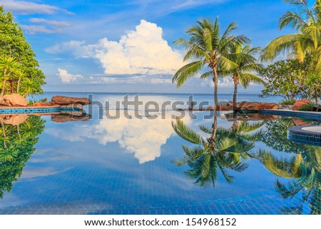 beautiful reflection of coconut trees and white cloud and blue sky on the swimming pool at the beach - stock photo