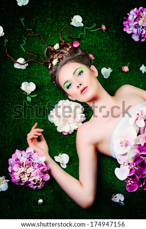 Beautiful relaxed woman lying on a grass surrounded by flowers. Beauty of spring and summer.  - stock photo