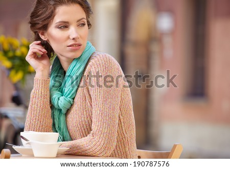 Beautiful relaxed woman smiling and enjoying the open air restaurant in the city  - stock photo