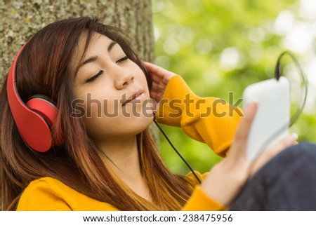 Beautiful relaxed young woman enjoying music in the park - stock photo