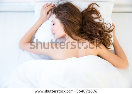 Beautiful relaxed young woman with long hair lying and sleeping on bed in bedroom - stock photo
