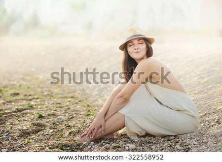 Beautiful relaxing woman sitting on a sand sea beach dressed in white dress with open back and hipster hat. - stock photo