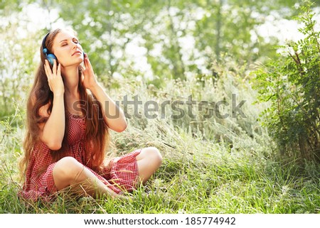 Beautiful Relaxing Young Woman with Headphones Outdoors