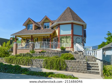 Beautiful residential house on blue sky background. Bed and breakfast hotel in British Columbia, Canada.  - stock photo