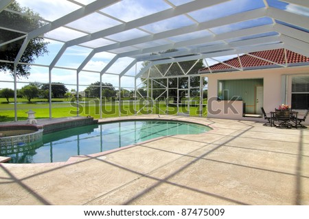 Beautiful residential screened-in swimming pool with patio and patio furniture with room for your copy - stock photo