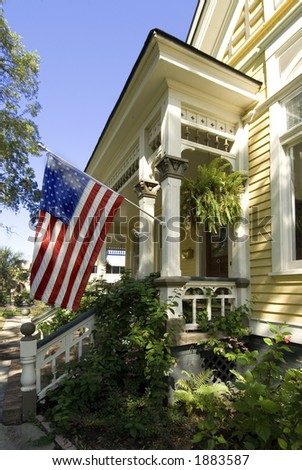 Beautiful restored old turn of the century home proudly displaying an American Flag - stock photo