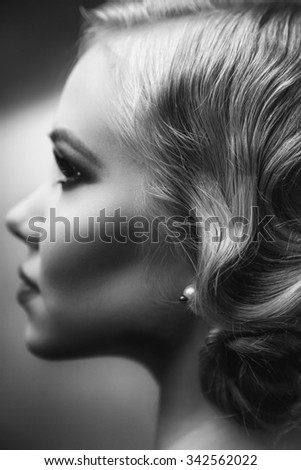Beautiful retro chic blonde girl in black dress wearing pearls. Beauty Retro Woman Portrait. Glamour Lady. Vintage styled Girl with perfect make up and hairstyle. B&W Photo