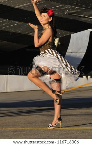 beautiful retro lady blowing a kiss under a wing of a WWII aircraft - stock photo