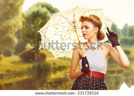 beautiful retro woman in vintage clothes with umbrella under the sun at the lake - stock photo
