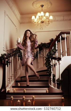 Beautiful rich woman on staircase with a candle