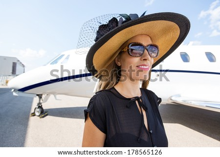 Beautiful rich woman standing against private jet - stock photo