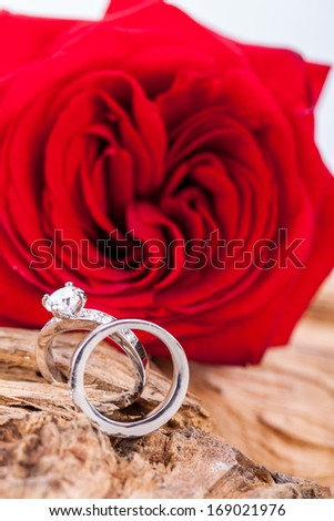 beautiful ring on wooden background and red rose present valentines